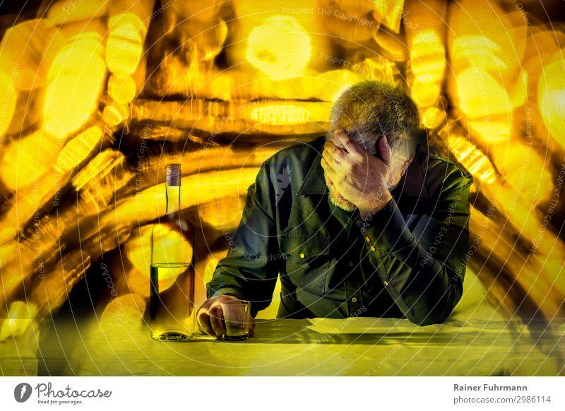 Ein Mann sitzt an einem Tisch und stützt seinen Kopf auf eine Hand. Vor ihm stehen eine Flasche Alkohol und ein Glas. Der Hintergrund leuchtet in grellen Farben.