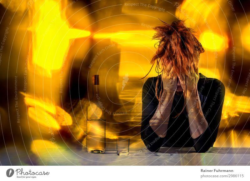An einem Tisch sitzt eine betrunkene Frau. Neben ihr steht eine Flasche mit Alkohol und ein Glas. Kräftige gelbe Lichter flackern im Hintergrund. Mensch feminin