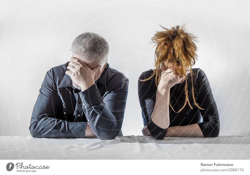 Ein Mann und eine Frau sitzen an einem Tisch, sie wirken deprimiert und schweigen Mensch maskulin feminin Erwachsene 2 Konflikt & Streit Traurigkeit warten