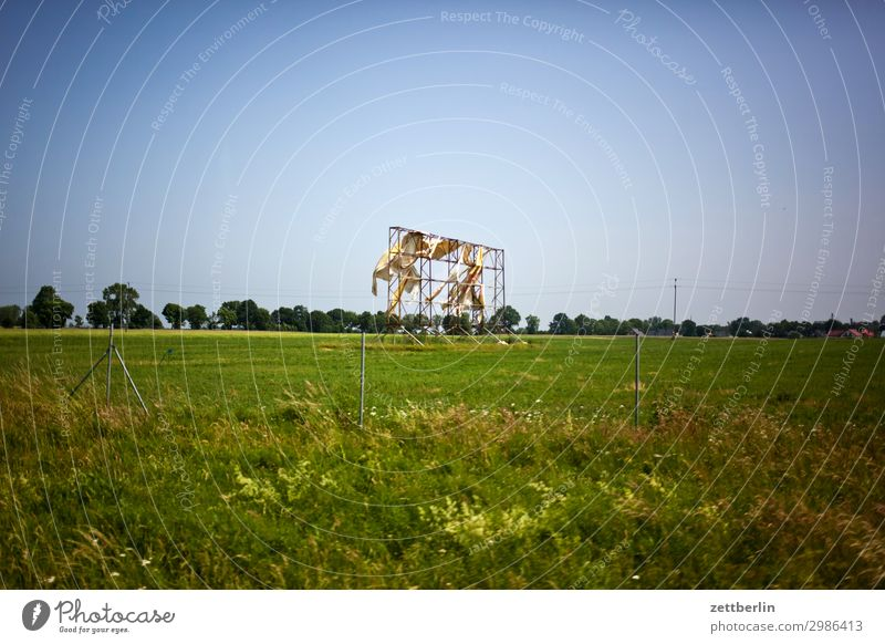 Hier könnte Ihre Werbung stehen! Werbebranche Transparente Außenaufnahme Umgebung Information Gestell Rahmen kaputt Wind wehen verweht Wiese Gras Weide Horizont