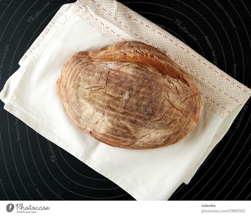 gebackenes ovales Roggenbrot Brot Ernährung Essen Tisch Küche Holz dunkel frisch natürlich braun schwarz Bäckerei Holzplatte Kruste Mehl Lebensmittel Korn