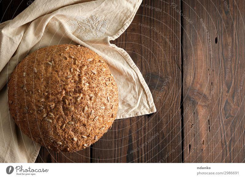 gebackenes rundes Roggenbrot mit Sonnenblumenkernen Brot Brötchen Ernährung Essen Frühstück Diät Tisch Holz dunkel frisch lecker natürlich oben braun Tradition