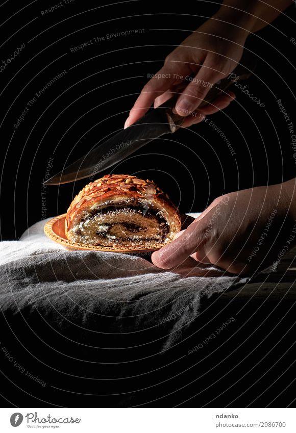 weibliche Hände schneiden gebackenes Brötchen mit Mohnblättern Teigwaren Backwaren Brot Dessert Messer Körper Tisch Frau Erwachsene Hand Holz Essen dunkel