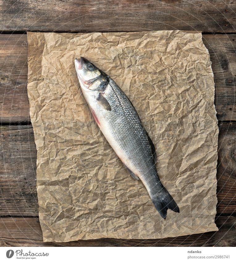 frischer ganzer Seebarschfisch auf braunem Knitterpapier Meeresfrüchte Ernährung Tisch Küche Natur Tier Papier Holz oben grau kulinarisch Feinschmecker