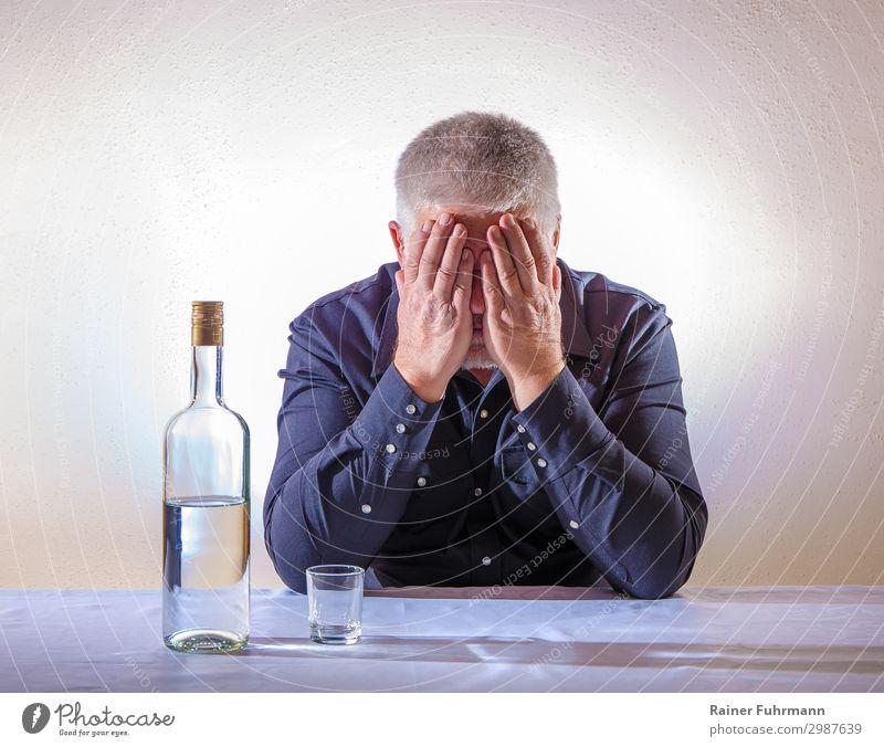 Ein Mann sitzt an einem Tisch und bedeckt mit den Händen sein Gesicht. Auf dem Tisch steht eine Flasche mit Alkohol und ein leeres Schnapsglas Wodka Alkoholiker
