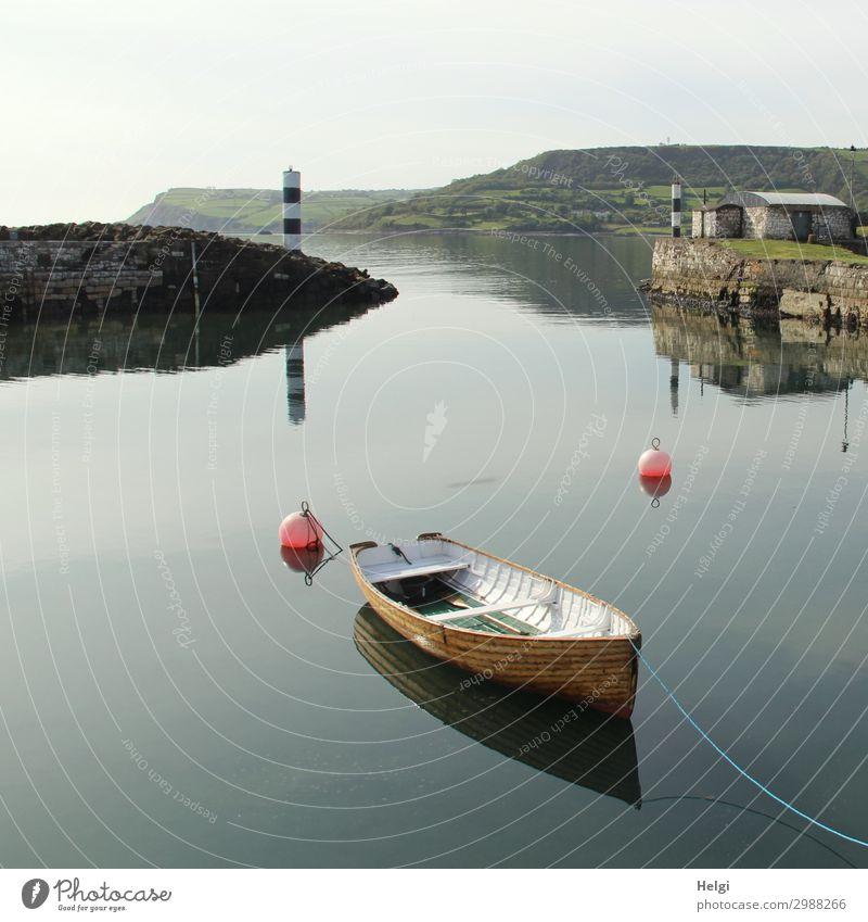 in einem kleinen Hafen in Irland liegt ein Holzboot in stillem Wasser mit Spiegelung, im Hintergrund ein schwarz-weißer Leuchtturm Umwelt Natur Landschaft