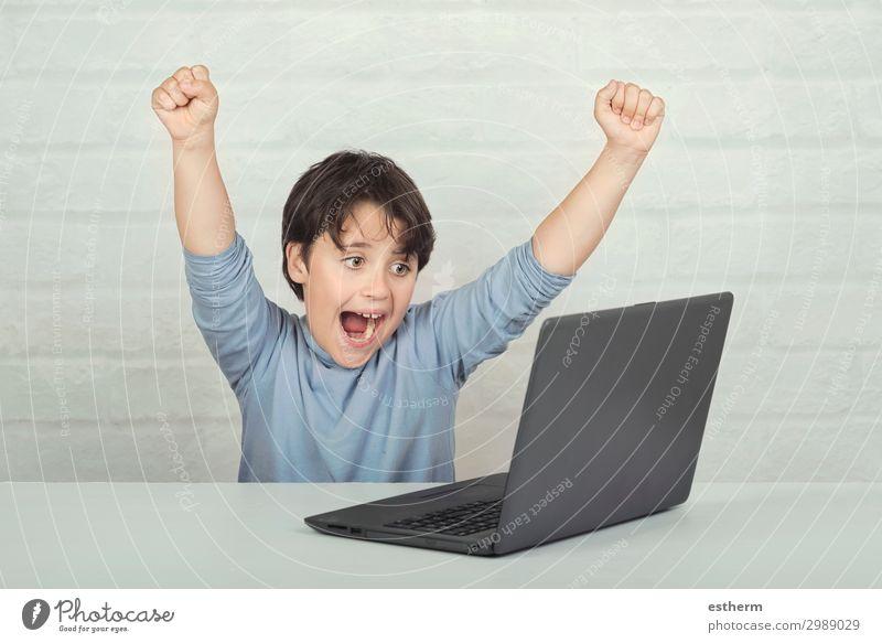 Glückliches Kind mit Laptop-Computer auf gemauertem Hintergrund Freude Freizeit & Hobby Spielen Entertainment Erfolg Schule Bildschirm Software
