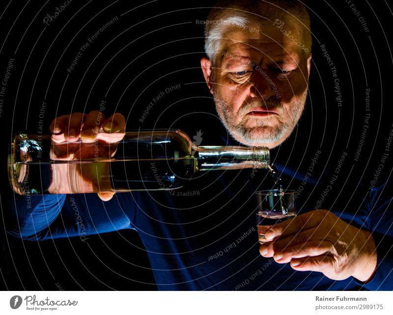 """Ein Mann gießt Alkohol in ein Glas Mensch maskulin Erwachsene 1 grauhaarig """"Flasche Schnapsglas Alkohol"""" trinken Alkoholsucht Sucht """"Alkoholismus Wodka süchtig"""