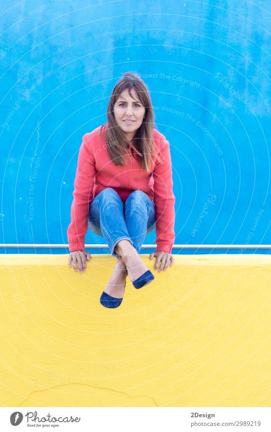 Frau in Jeans genießt an einer gelben Wand, während sie die Kamera betrachtet. Lifestyle Stil schön Erholung Mensch feminin Erwachsene Fuß 1 18-30 Jahre
