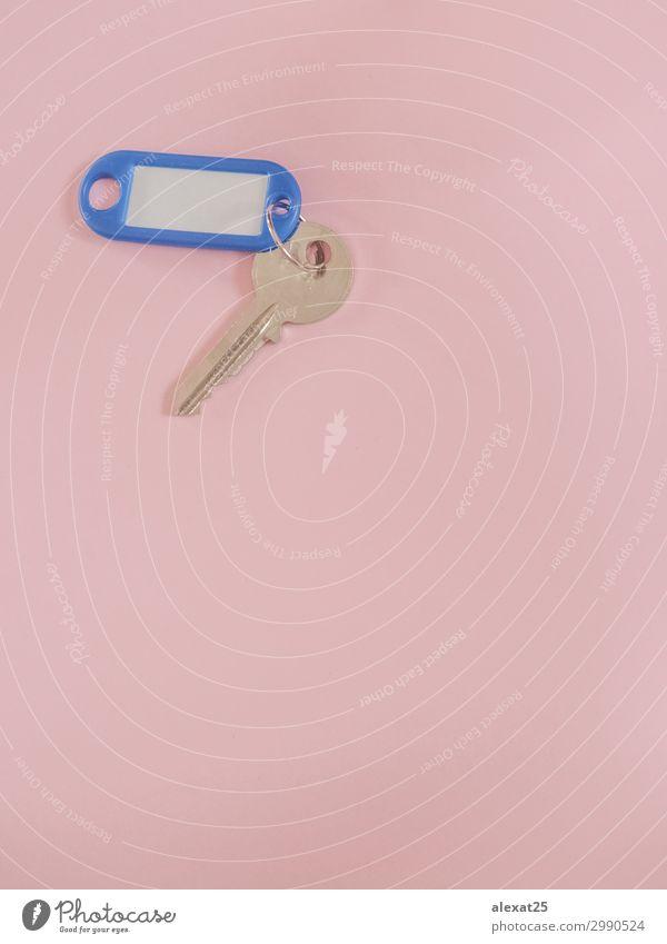 Ein Metallschlüssel mit leerer Beschriftung auf rosa Hintergrund mit Kopiermöglichkeit. Design Haus Business Sicherheit Geborgenheit geheimnisvoll Zugang blanko