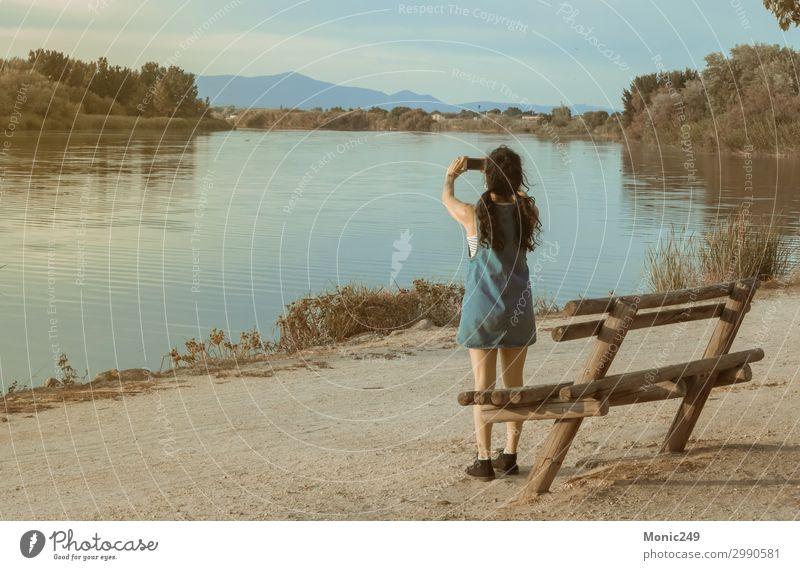 Brünette Frau, die mit einem Handy einen Fluss fotografiert. Erholung Modellbau Ferien & Urlaub & Reisen Abenteuer Sommer Sommerurlaub Berge u. Gebirge sprechen