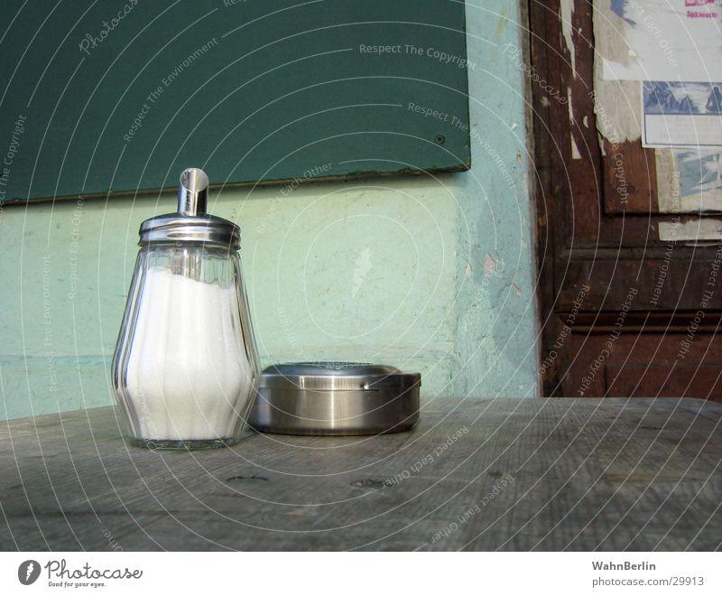 Tisch im Café Holz Aschenbecher Stillleben rustikal Dinge Metall Glas Zuckerstreuer Außenaufnahme
