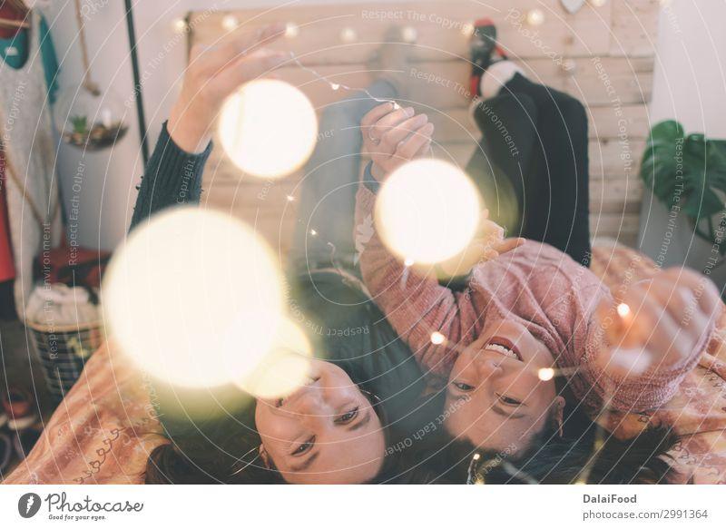 Mädchen spielen mit Weihnachtslichtern im Bett Weihnachten & Advent Freundschaft Familie & Verwandtschaft Glück 18-30 Jahre neu Feste & Feiern heimwärts Winter