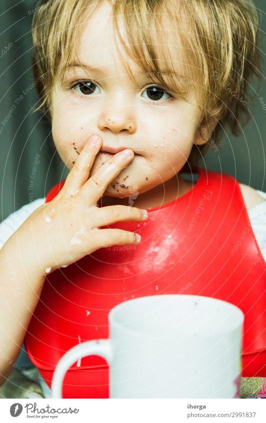 Porträt bezauberndes Kind isst Schokolade Biskuitkuchen Attribut Baby Hintergrund Lätzchen Junge braun Kuchen Bonbon Kindheit schoko niedlich lecker wüst