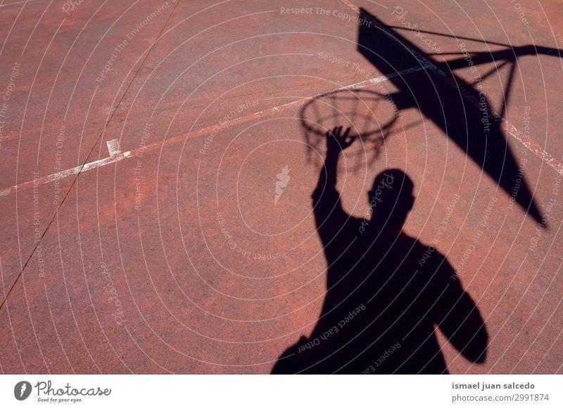 Mann spielt Basketball Schatten Silhouette auf der Straße Korb Sonnenlicht Boden Spielfeld Etage Sport Spielen aussetzen Park Spielplatz Außenaufnahme