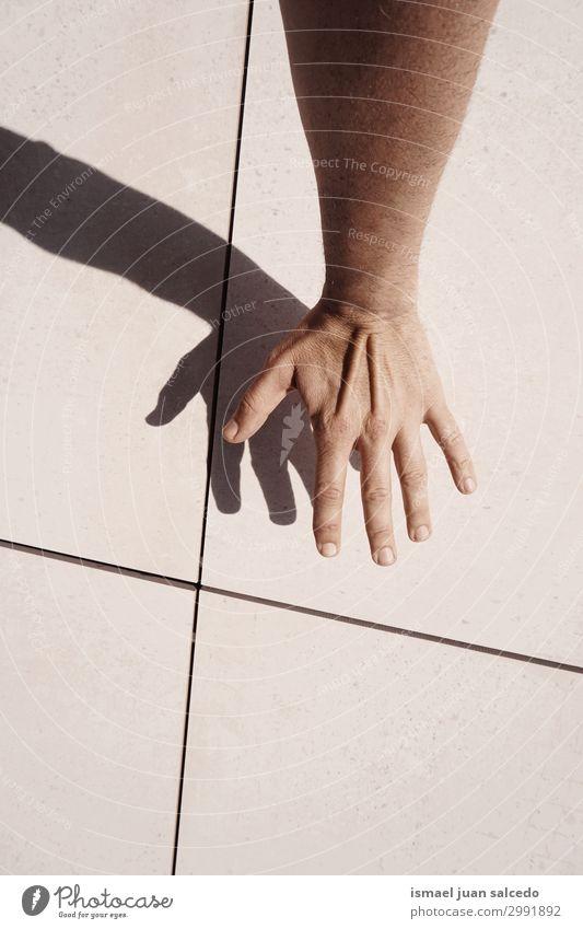 Mann Hand Schatten Silhouette an der Wand in der Straße Finger Handfläche Körperteil Handgelenk Arme Haut Mensch Lichterscheinung Sonnenlicht gestikulieren