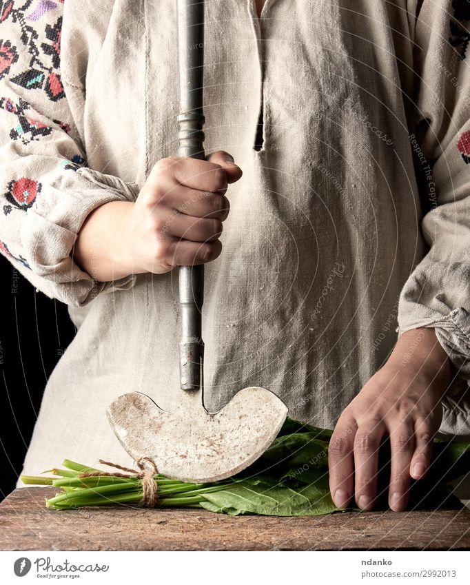 Frau in einem grauen Kleid schneidet Blätter von frischem Sauerampfer. Gemüse Salat Salatbeilage Kräuter & Gewürze Ernährung Vegetarische Ernährung Messer Tisch