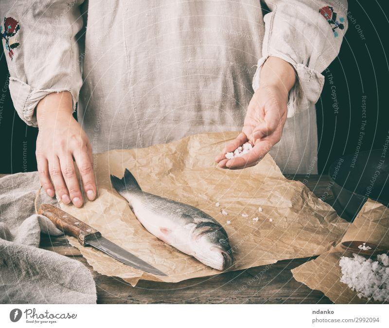 frischer ganzer Seebarschfisch auf braunem Papier liegend Fleisch Fisch Meeresfrüchte Kräuter & Gewürze Ernährung Tisch Küche Werkzeug Mensch Hand Tier Holz