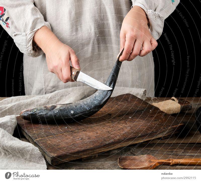 Frau in grauer Leinenkleidung reinigt den Fisch Seebarsch. Meeresfrüchte Messer Tisch Küche Werkzeug Erwachsene Hand Finger Holz alt machen frisch Sauberkeit