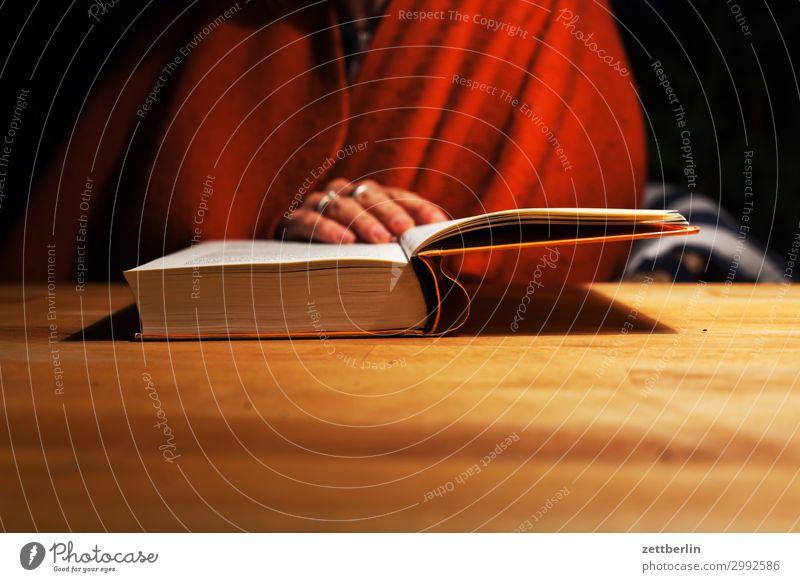 Ein neues Buch Frau Mensch Hand Erholung dunkel Textfreiraum sitzen Tisch Beginn lesen festhalten gemütlich Bibliothek Literatur Tischplatte