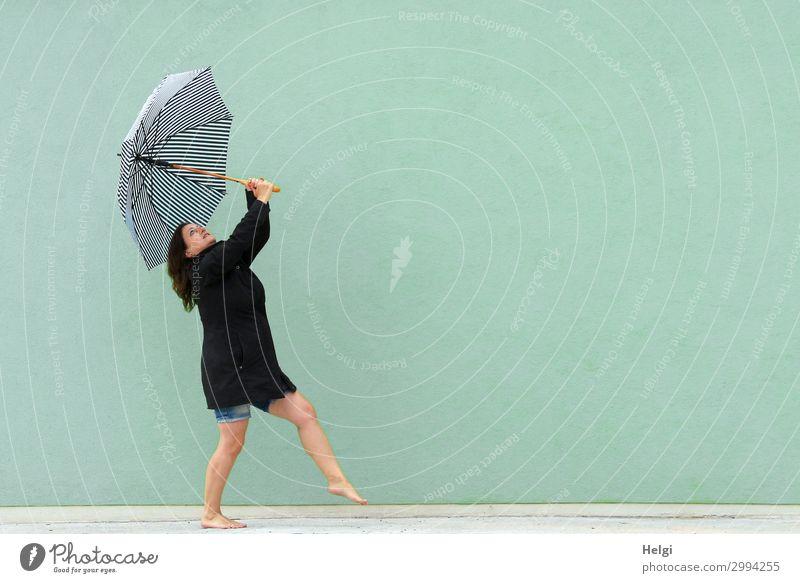 Frau mit schwarzem Mantel und kurzer Jeans tanzt barfuß mit einem Regenschirm in den Händen vor einer hellgrünen Wand Mensch feminin Erwachsene 1 45-60 Jahre