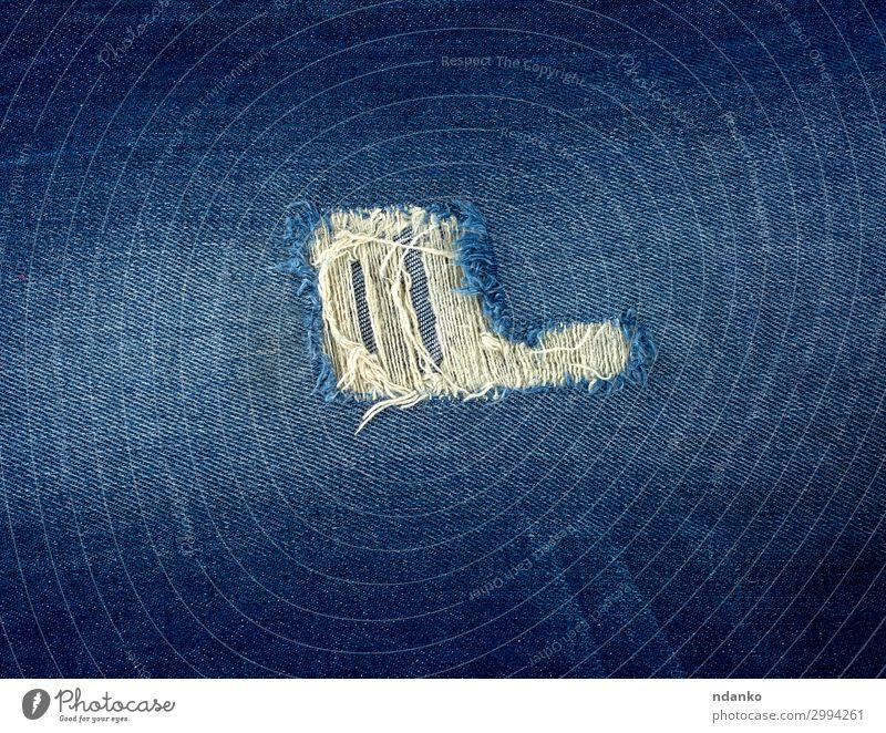Fragment aus Blue Jeansstoff mit einem Loch Stil Design Mode Bekleidung Hose Jeanshose Stoff alt blau Farbe Schaden Hintergrund Sehne abgenutzt gerissen
