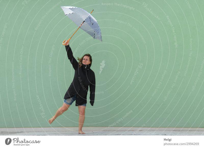 Frau mit dunkler Jacke und kurzen Jeans steht barfuß auf einem Bein vor hellgrüner Wand und hält einen Regenschirm hoch Mensch feminin Erwachsene 1 45-60 Jahre