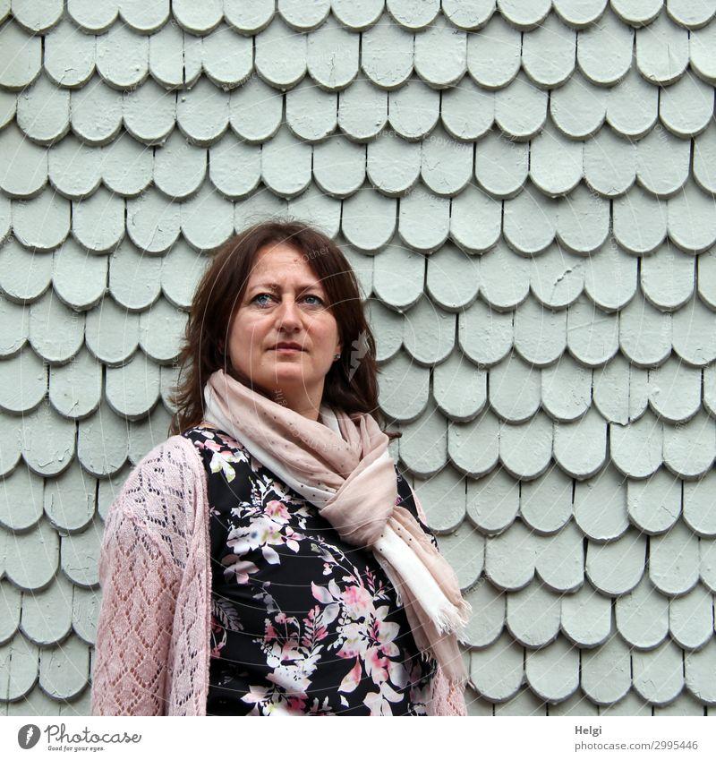 Frau mit dunklen langen Haaren , buntem Kleid, rosa Strickjacke und rosa Schal steht vor einer grauen Wand aus Holzschindeln Mensch feminin Erwachsene 1