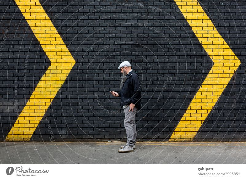 Mann vor einer schwarzen Wand mit gelben Pfeilen Mensch Stadt Erwachsene Bewegung Mauer Fassade maskulin Schilder & Markierungen Energie Hinweisschild Zeichen