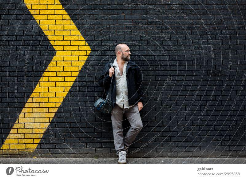 Mann vor einer schwarzen Wand mit gelben Pfeilen Mensch maskulin Erwachsene 1 Schilder & Markierungen rechts links Bewegung Richtung richtungweisend