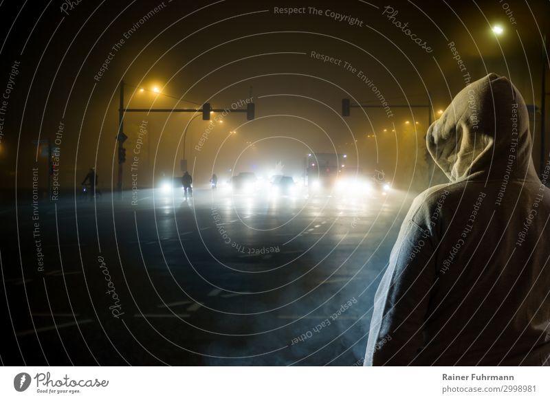 ein Mann beobachtet nachts den Strassenverkehr Mensch Stadt Straße Erwachsene PKW Verkehr Nebel Fahrrad Fahrradfahren beobachten bedrohlich