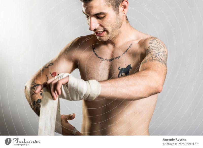 Muai thailändischer Kämpfer, der im Studio posiert und mit Tattoos geschossen wird. Sport Junge Mann Erwachsene Ring Handschuhe Fitness Aggression stark Wut