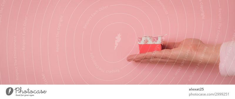 Hand mit einem Geschenk auf rosa Hintergrund mit Kopierfläche Dekoration & Verzierung Feste & Feiern Geburtstag Mensch Frau Erwachsene Papier Paket Schnur weiß