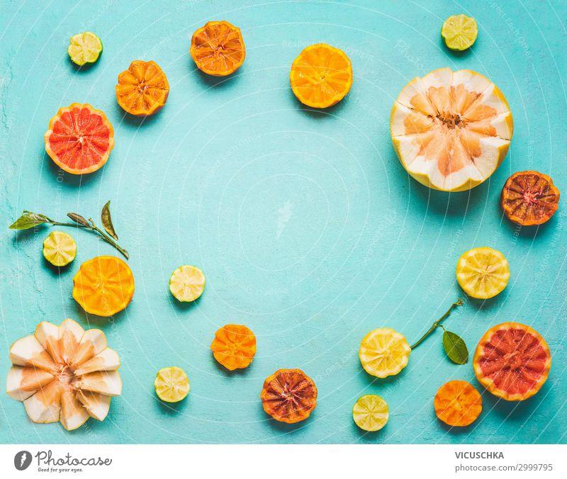 Rahmen aus verschiedenen bunten Zitrusfrüchtehälften mit grünen Blättern auf hellblauem Hintergrund, Draufsicht. Kopierfläche für Ihren Entwurf. Flach gelegt. Konzept für gesundes Essen und Lebensstil. Quelle von Vitamin C