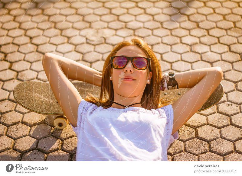 Junges Mädchen mit einem Skateboard, das im Sommer auf der Straße liegt. Lifestyle Stil Freude Glück schön Freizeit & Hobby Sport Mensch Frau Erwachsene
