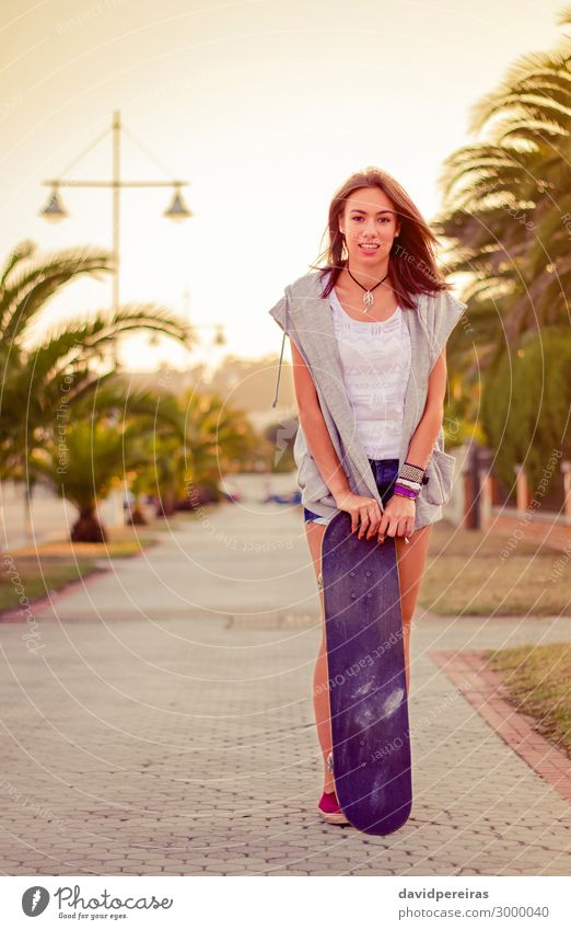Junges Mädchen mit einem Skateboard im Sommer im Freien. Lifestyle Stil Freude Glück schön Freizeit & Hobby Sport Mensch Frau Erwachsene Jugendliche Wärme Baum