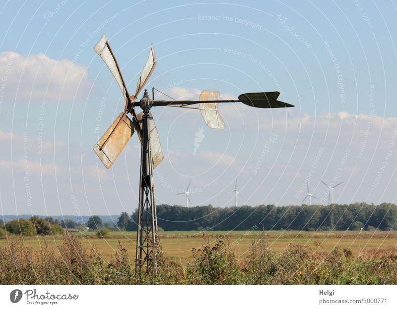 kleines historisches Windrad aus Metall steht auf einer Wiese, in der Ferne stehen moderne Windkraftanlagen Technik & Technologie Energiewirtschaft