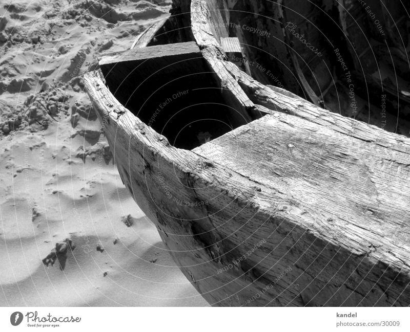 Gestrandet Wasserfahrzeug Holz Strand schwarz weiß morsch Meer historisch alt Sand Schiffsplanken Kontrast Wind