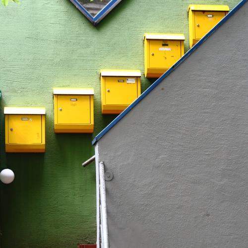 Post Stadt Stadtzentrum bevölkert Haus Mauer Wand Treppe Briefkasten Häusliches Leben gelb grün Postbote Farbfoto Außenaufnahme Menschenleer Textfreiraum rechts
