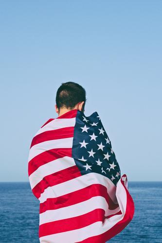 Mann von hinten in amerikanische Flagge gehüllt gegen blauen Himmel. Glück Freiheit Meer Feste & Feiern Erwachsene Hand Denkmal Streifen Fahne Ehre