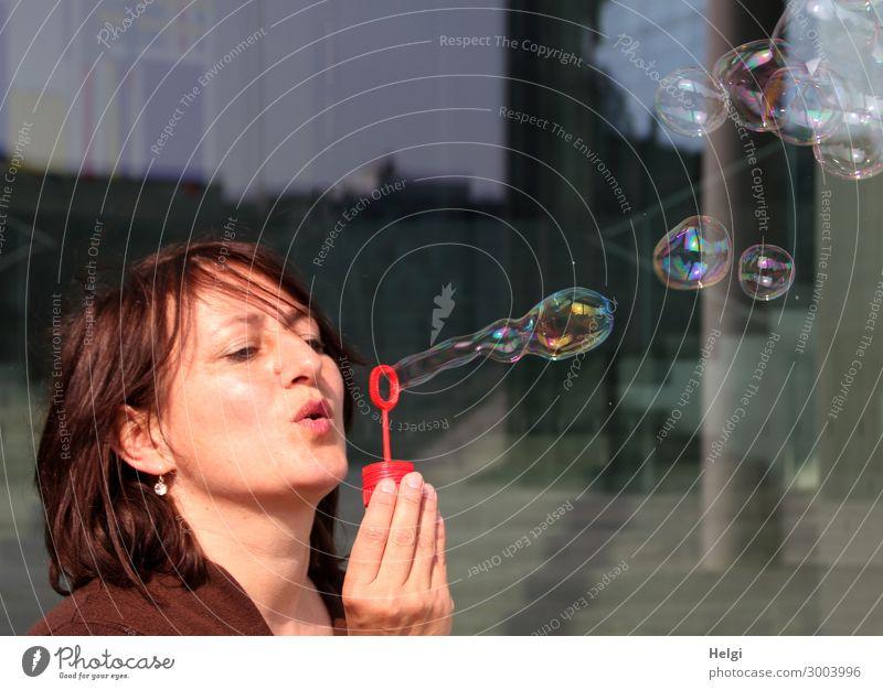 Frau mit brünetten langen Haaren pustet Seifenblasen Mensch feminin Erwachsene Kopf Haare & Frisuren Hand Finger 1 45-60 Jahre festhalten außergewöhnlich