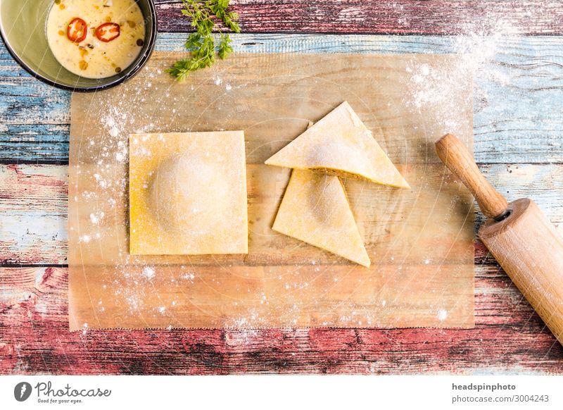 Selbsgemachte Tortelloni auf buntem Holztisch Lebensmittel Teigwaren Backwaren Ernährung Mittagessen Abendessen Festessen Slowfood Italienische Küche