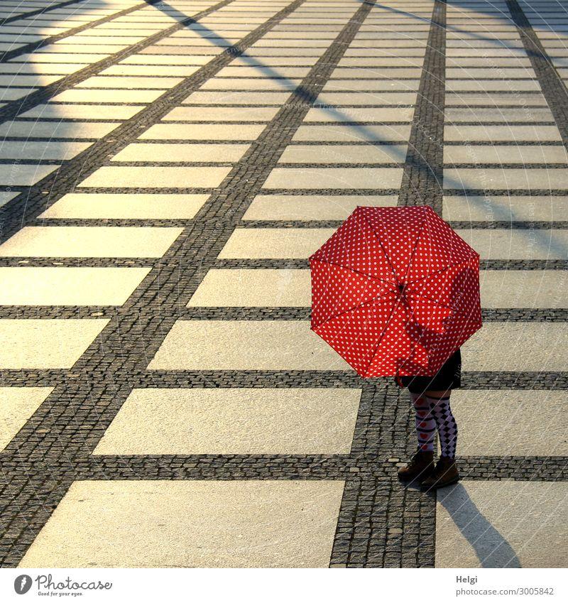 Weibliche Person steht mit einem rot-weiß gepunkteten Regenschirm und gemusterten Strümpfen auf einem großen gepflasterten Platz im Gegenlicht Mensch feminin