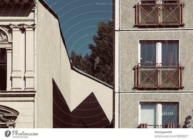 Zwei unterschieldiche Hausfassaden nebeneinander vor einem blauen Himmel Stadt Hochhaus Mauer Wand Fassade eckig trist Fenster Zacken Schatten Häusliches Leben