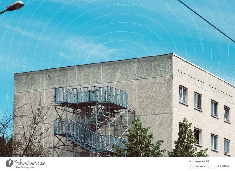 Hochhaus mit Feuertreppe Kleinstadt Stadt Menschenleer Haus Mehrfamilienhaus Fenster Dach Feuerleiter Treppe eckig einfach hässlich trist Himmel blau grau