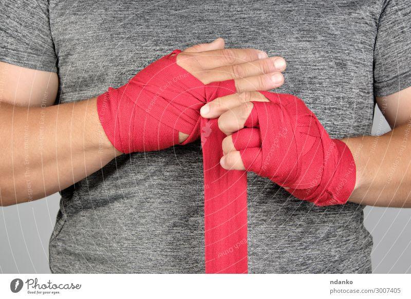 Sportlerhände eingewickelt in eine rote elastische Sportbinde Lifestyle Körper sportlich Fitness Mensch maskulin Mann Erwachsene Hand Bewegung stehen Aggression