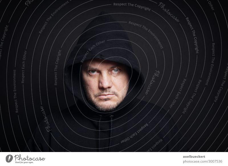 Mann in schwarzem Hoodie schaut finster Hooligan Mensch maskulin Erwachsene 1 30-45 Jahre 45-60 Jahre Pullover Mütze Bart Dreitagebart Vollbart bedrohlich