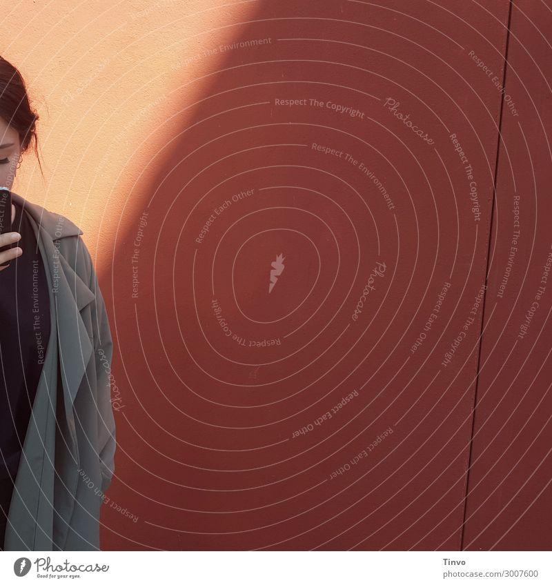 Frau mit Handy vor rötlicher Wand Mensch Jugendliche Junge Frau 18-30 Jahre Erwachsene Mauer Kommunizieren Aktion Information brünett Informationsaustausch