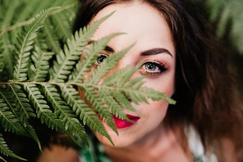Nahaufnahme des Porträts einer jungen, schönen Frau unter grünem Farn Lifestyle Haut Gesicht Schminke Wellness Spa Freizeit & Hobby Garten feminin Junge Frau