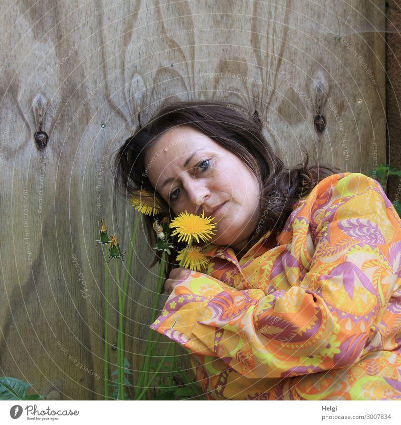 Porträt einer Frau mit langen, brünetten Haaren und bunter Bluse hält eine Löwenzahnblume in der Hand, im Hintergrund eine Holzwand Mensch feminin Erwachsene 1